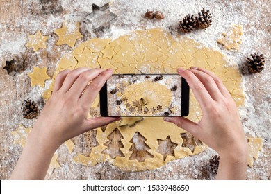 Top view of hands of a person making photos with the mobile phone to the raw dough to make Christmas tree shaped cookies and star shapes. On a floured table with pineapples. Christmas desserts