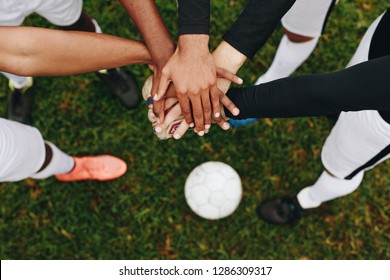Top view of hands of players placed one over the other standing in a huddle. Players standing in a huddle joining their hands together in the centre with a soccer ball on the ground.