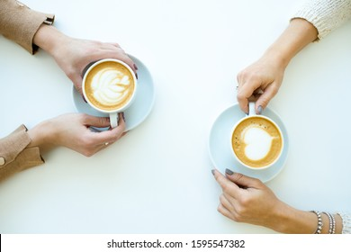 Top view of hands of two friendly females holding cups with cappuccino while relaxing by table in cafe