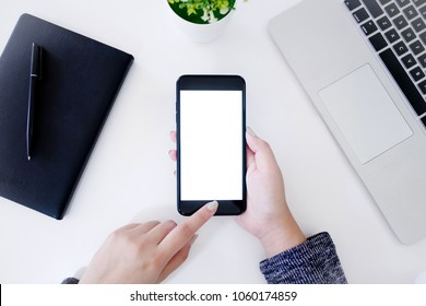 top view of hands using blank screen mobile smart phone with notebook and laptop