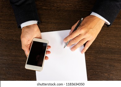 Top view of Hands using phone and paper list on wood table.