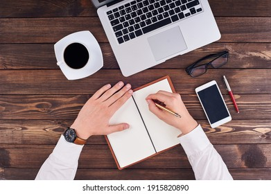 top view of hands writing in notepad, laptop, phone, pen and glasses on table in office.