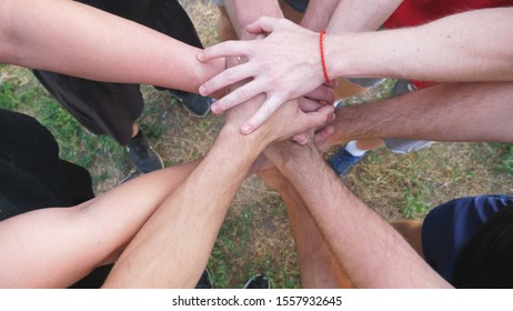 Top view hands of young athletes stacking together one by one in unity. Group of best friends putting their arms in centre of a circle and raising them up. Concept of friendship and teamwork. Slow mo.