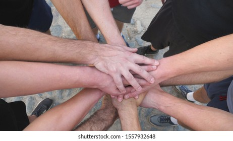 Top view hands of young sportsmen stacked together one by one in unity. Group of best friends putting their arms in centre of a circle as symbol of friendship and teamwork. Close up Slow motion.