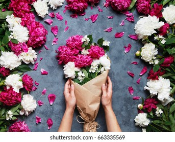 Top view of hands of young woman florist holding beautiful bouquet of peonies. Florist at work: pretty woman making summer bouquet of peonies on a working gray table. Flat lay composition.