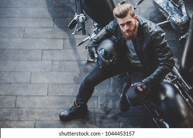 Top view of handsome bearded man in motorcycle shop. Biker is choosing new vehicle and motorcycle accessories. Sitting with helmet in hands. Safety driving concept.
