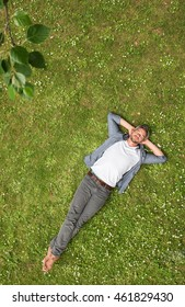 Top view. Handsome grey haired man  lying in the grass, relaxing by a beautiful day in summer