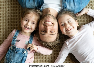 Top view of handsome young father and his cute little daughters looking at camera and smiling, lying on floor.