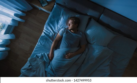 Top View of Handsome Young Man Sleeping Cozily on a Bed in His Bedroom at Night. Blue Nightly Colors with Cold Weak Lamppost Light Shining Through the Window.