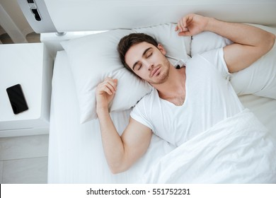 Top view of handsome young man in white t-shirt sleeping in bed