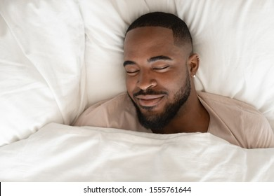 Top view of happy african American man sleeping in comfortable white bed seeing good pleasant dreams, calm biracial male feel fatigue resting napping in cozy bedroom under linen bedding sheets