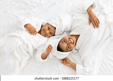 Top View Of Happy African Mom And Daughter In Bathrobes And With Towels On Head Lying On Bed, Relaxing Together After Bath, Ready For Beauty Treatments, Looking And Smiling At Camera, Free Space