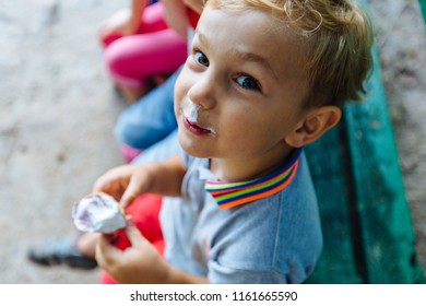 Top view of happy blond child boy with friends eating ice-cream outdoors in park.