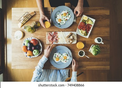 Top view of happy couple sitting at the kitchen table and having breakfast of fried eggs and vegetables