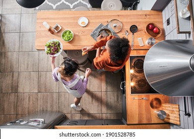 Top view of the happy curly multiracial woman giving a piece of cheese for her bestie while grated cheese at the pasta. Her bestie pouring salad at table. Friends cooking meal together at home. Stock