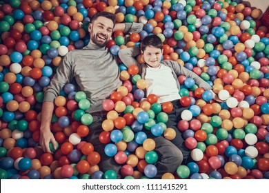 Top view. Happy dad and son in pool with balls. Family rest, leisure concept. Spending holiday together. Entertainment center, mall, amusement park.