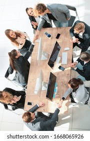top view. happy employees shaking hands during a meeting
