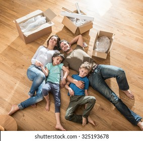Top view of a happy family in casual clothes laying on the wooden floor of their new flat with cardboard boxes around them They are looking at camera The smiling parents are holding their two children