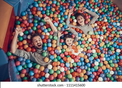 Top view. Happy family lying in pool with balls. Family rest, leisure concept. Spending holiday together. Entertainment center, mall, amusement park.