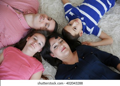 Top view of happy family portrait lying on fur carpet indoors