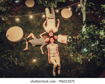 Top view of happy family is spending time together in park in the evening with garland of light bulbs. Parents with children having fun and enjoying being together. Mom, dad, son and daughter outdoors