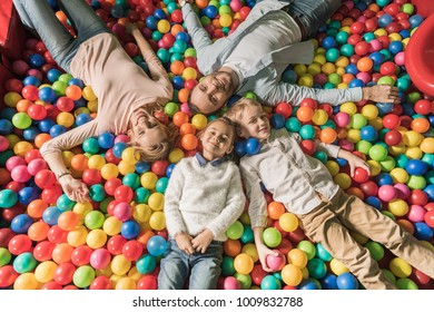 top view of happy family with two kids smiling at camera while lying in pool with colorful balls