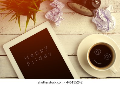 Top view of Happy Friday on digital tablet's screen with smiling face on coffee cup