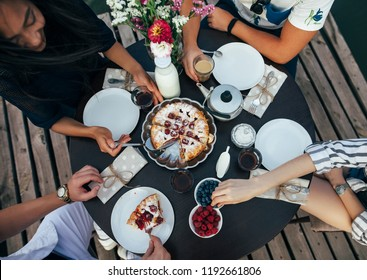 Top view of happy friends eating pie together. Food, dining and family concept