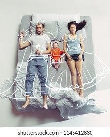 Top view of happy funny family with one newborn child in bedroom.  Happy family in bed and their dreams about dream fairy, tale, king, queen, princess, legend, crown. Painted dreams concept