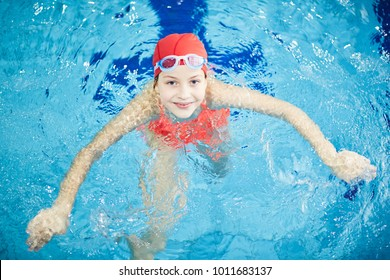 Top view of happy girl looking at camer out of clear transparent water of swimming-pool