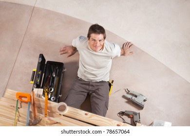 Top view of a happy handsome man with carpentry tools around