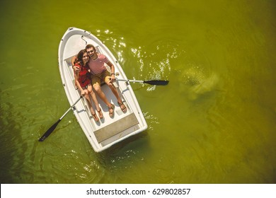 Top view of happy loving couple rowing a small boat on a lake. A fun date in nature. Couple hugging in a boat