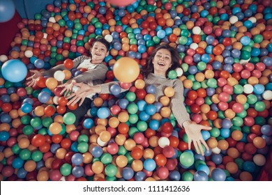 Top view. Happy mom and son in pool with balls. Family rest, leisure. Spending holiday together with family. Entertainment center, mall, amusement park.