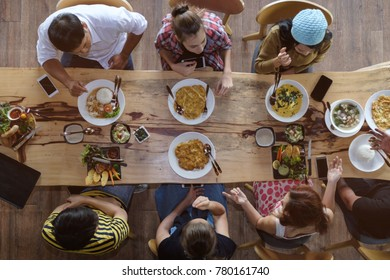 Top view of happy people gathering for eating food together and enjoying the party and communicate with family and friends at table on holiday, soft focus background