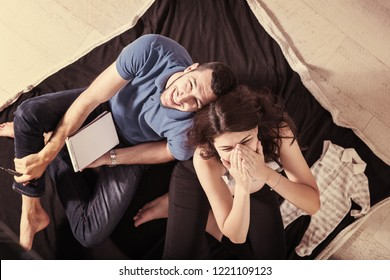 top view of a happy pregnant couple checking a list of things for their unborn baby at home on the floor