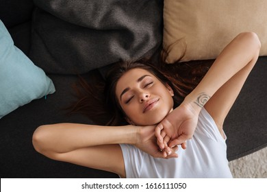 top view of happy tattooed girl with closed eyes chilling on sofa