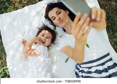 Top view of happy young beautiful mother blowing kiss and taking self portrait with cute daughter smiling during picnic lying on grass and white blanket. Motherhood, technology and childhood concept.