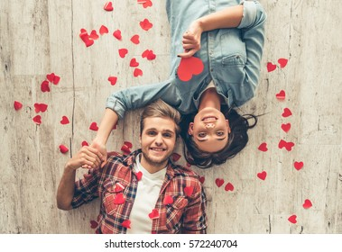 Top view of happy young couple looking at camera and smiling while lying on wooden floor. Girl is holding a red paper heart