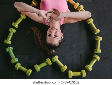 Top view happy young fitness woman in sports wear laying on floor and showing heart shape by hands while resting after training in gym. Beautiful sports girl lying among dumbbells in form of heart
