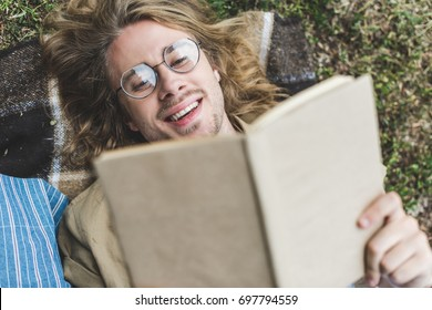 top view of happy young man reading book