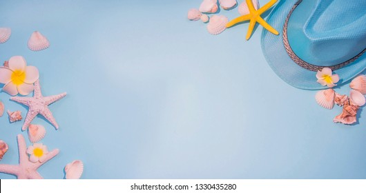 top view of hat and sea shell on light blue paper plank floor for summer vacation time background