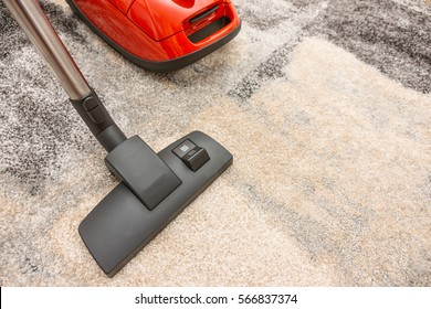 Top view of the head of a modern vacuum cleaner being used while vacuuming a carpet