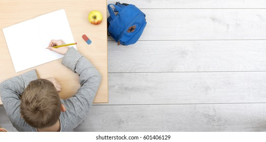 top view header of boy working behind school desk in classroom