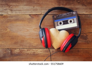 Top view of headphones with fabric heart next tape cassette over wooden background