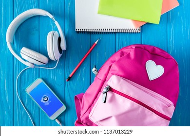 top view of headphones, pink backpack, smartphone with shazam application and stationery on blue wooden background