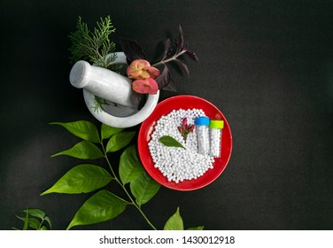Top View - Healing herbs, pink flower and a mortar, white sugar pills in red bowl on a black background. Homeopathic medicine grains scattered on a red plate with green leaf on the black surface