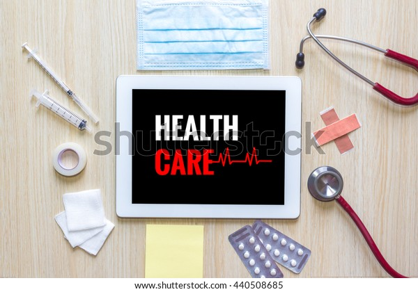Top view of Health care word on tablet with stethoscope, hypodermic syringe, medicine, mask and note.