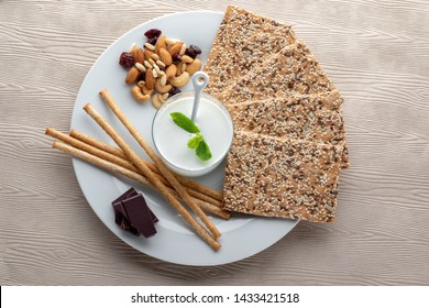 Top view of healthy afternoon diet snack.Organic kefir with sesame seed crackers, bread sticks, dark chocolate and variety of nuts.