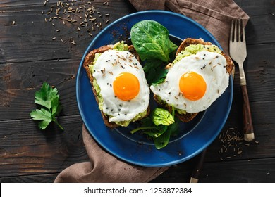 Top view healthy avocado toasts for breakfast or lunch with rye bread, avocado puree toast and fried eggs on dark wooden table