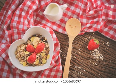 Top view of healthy breakfast with cereal and fresh strawberry in the love cup . Decorated with happy wooden spoon and milk. Concept about love and relationship. Vintage Style